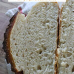 Pinterest pin for artisan bread with an image of a loaf of bread sliced open to reveal the soft crumb.