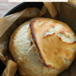 Pinterest pin for artisan bread with an image of a loaf of bread in a cast iron pan.