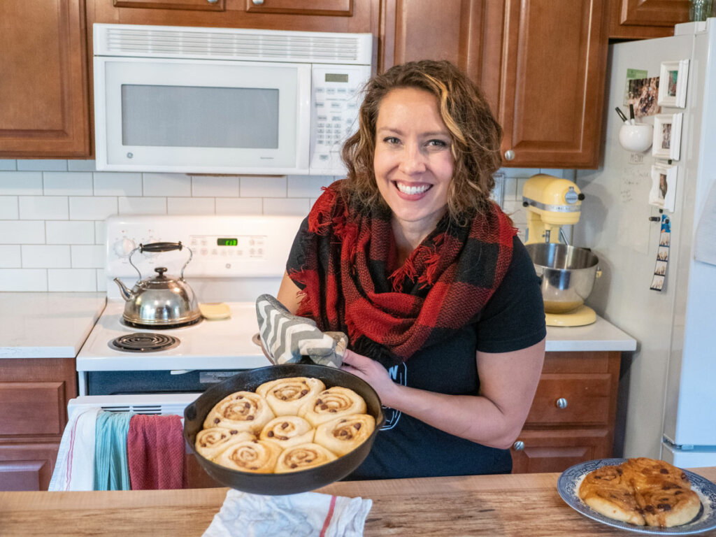A woman holding up a cast iron pan of cinnamon rolls.