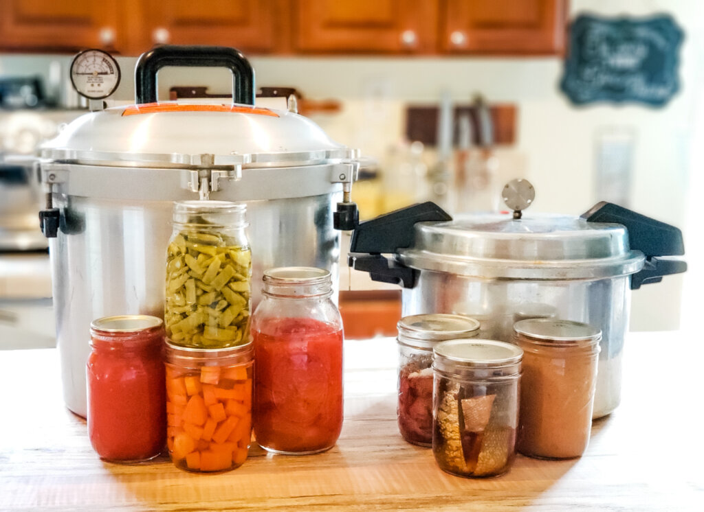 Two pressure canners and jars of home canned food sitting on a kitchen counter.