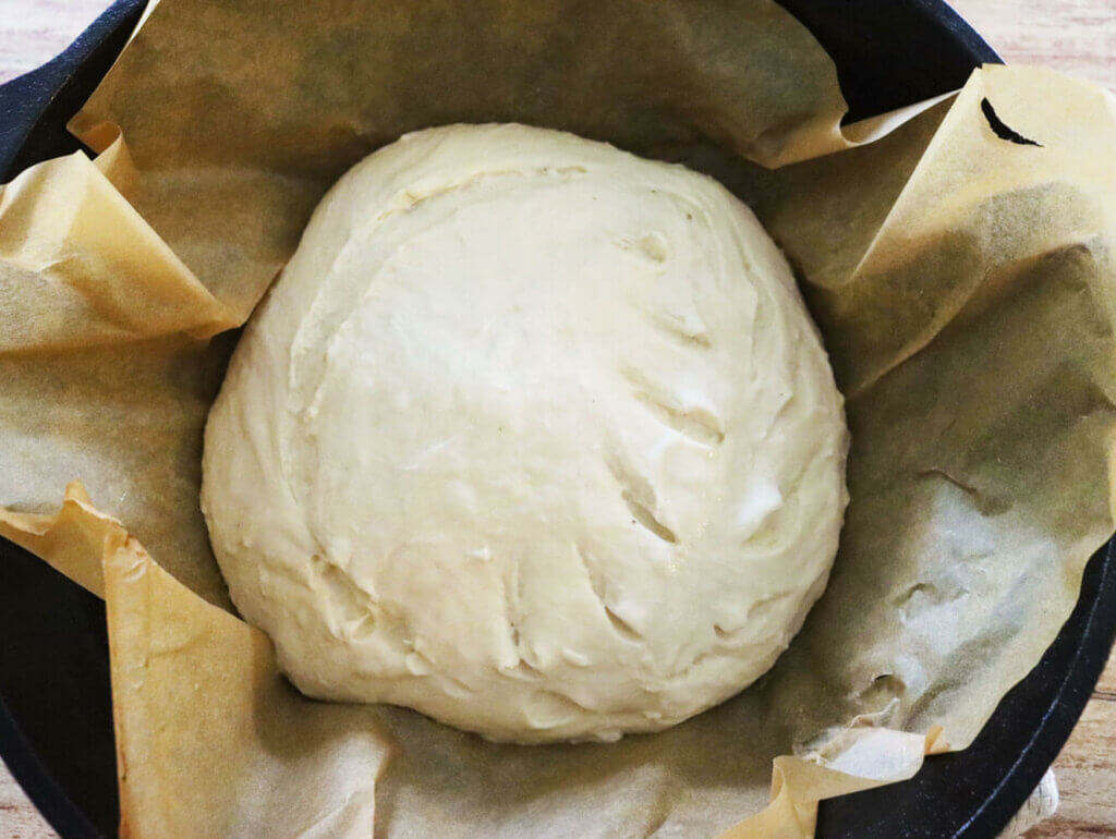 Artisan bread dough shaped and scored on parchment paper in a cast iron dutch oven.