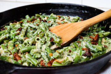 Cast iron skillet with green bean casserole and a wooden spoon.