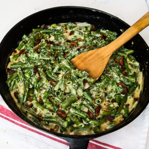 Cast iron pan with green bean casserole and a wooden spoon.