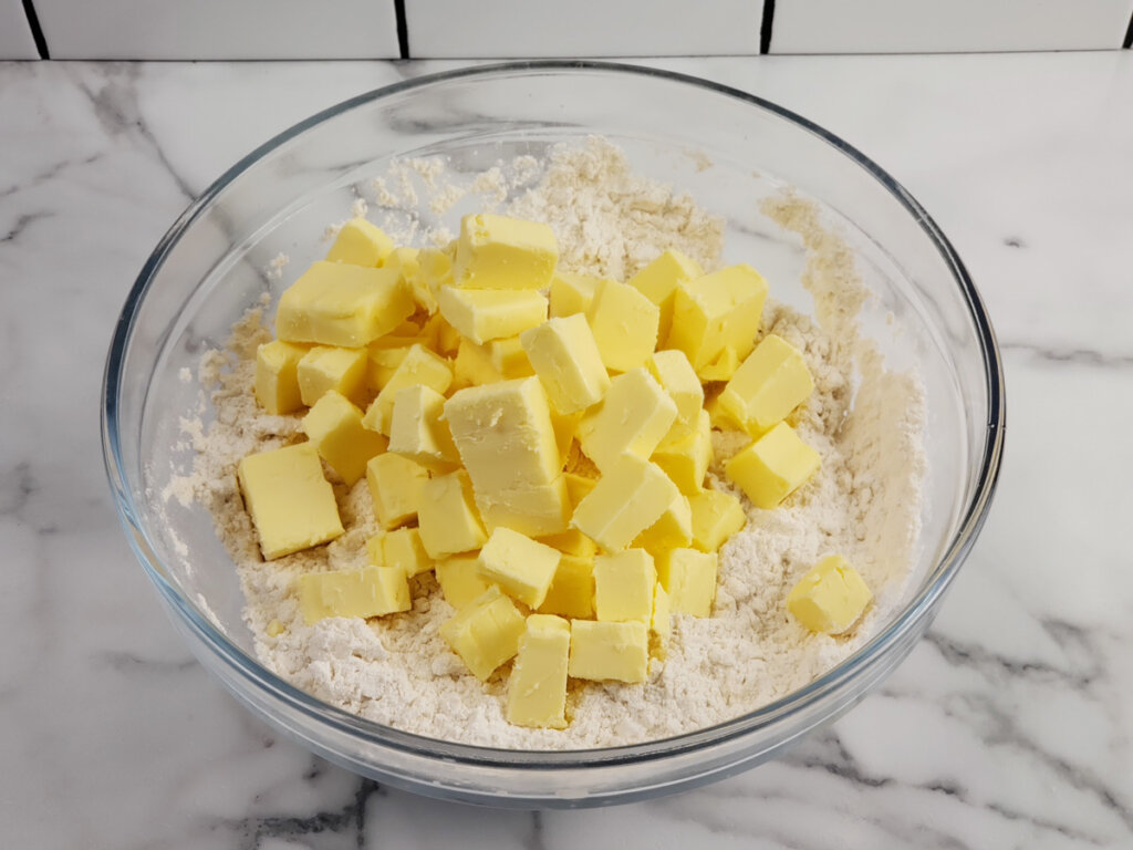 A bowl of flour topped with cubed butter.