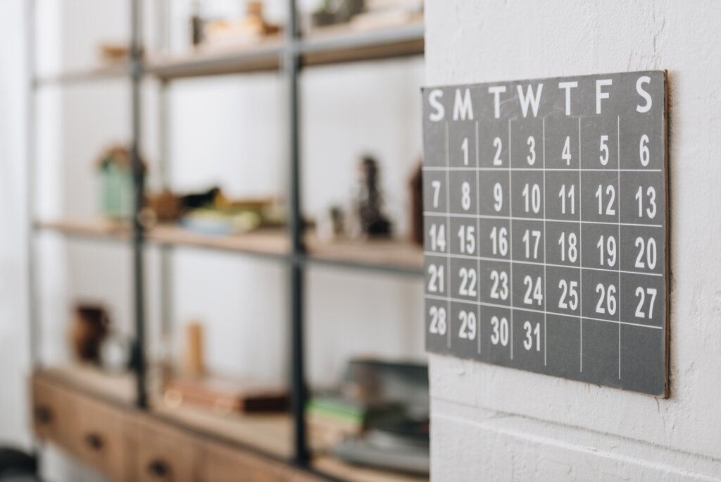 A one month calendar hanging on the wall.