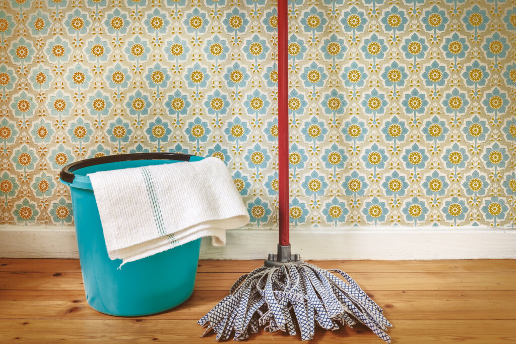 A mop and a bucket leaning against a wallpapered wall.