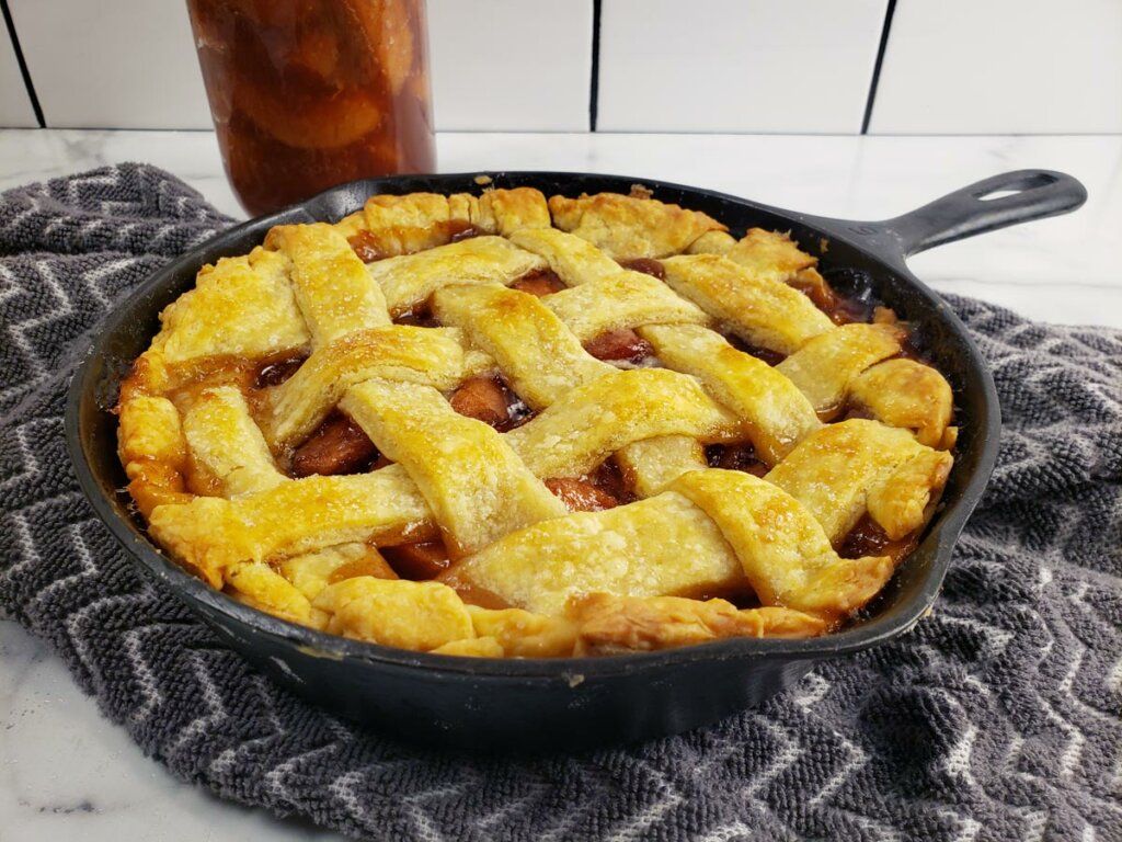 Apple pie with a lattice crust in a cast iron skillet with canned apple pie filling in the background.