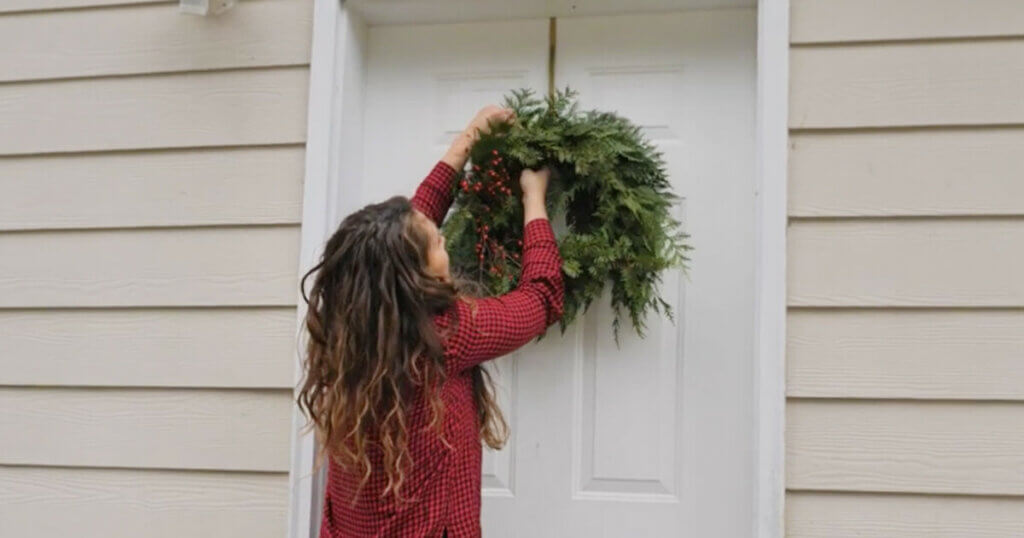 A woman hanging a Christmas wreath on her front door.