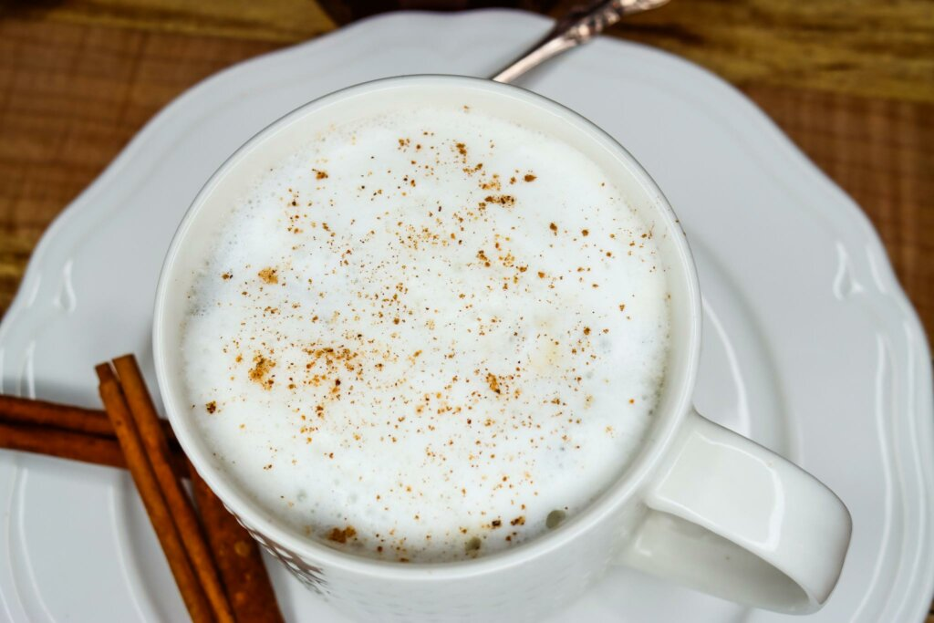 Upclose photo of a chai tea latte in a white mug on a white saucer.