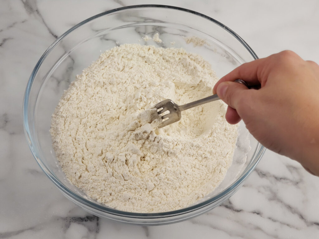 Flour and salt being stirred together in a glass bowl with a fork.