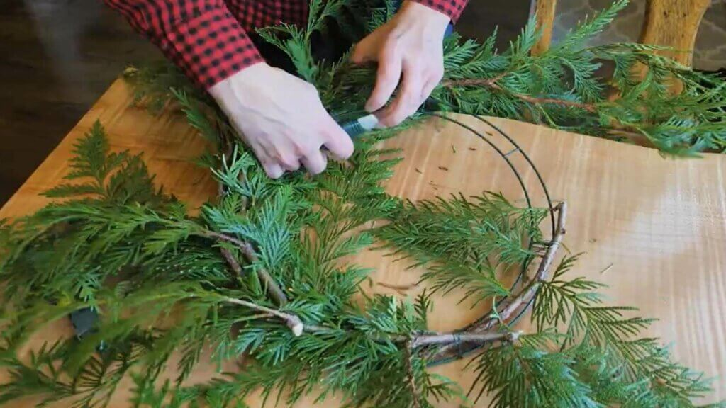 Hands securing evergreen boughs to a wreath form.