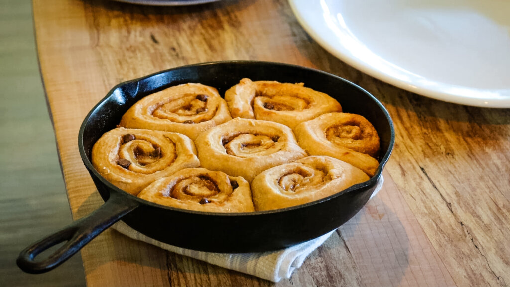 Chocolate caramel cinnamon rolls baked in a cast iron pan sitting on a table.
