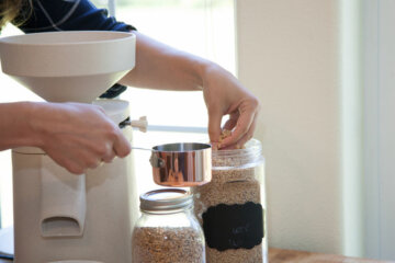 A woman's hand putting whole grain into a measuring cup with a Mockmill home grain mill in the background.