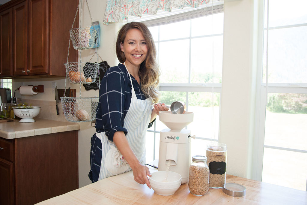 Woman standing next to a Mockmill grain mill in her kitchen.