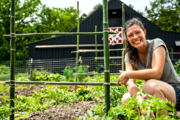A woman crouched down in her garden.