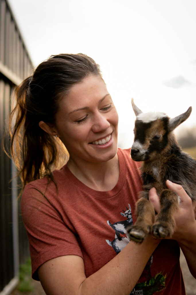 A woman holding a baby goat.