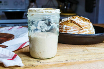 Sourdough starter in a jar with a loaf of bread in the background.
