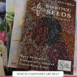 "Pinterest pin with a photo of a stack of seed catalogs. Text overlay says, ""Buying the best heirloom seeds""."