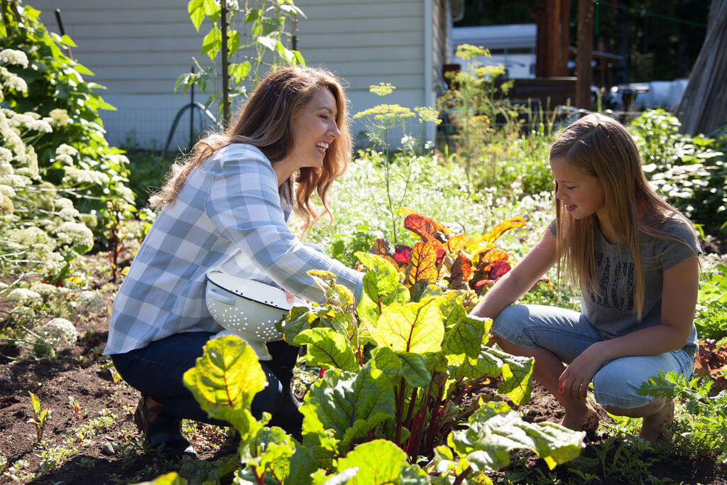 A woman and daughter picking vegetables in the garden.