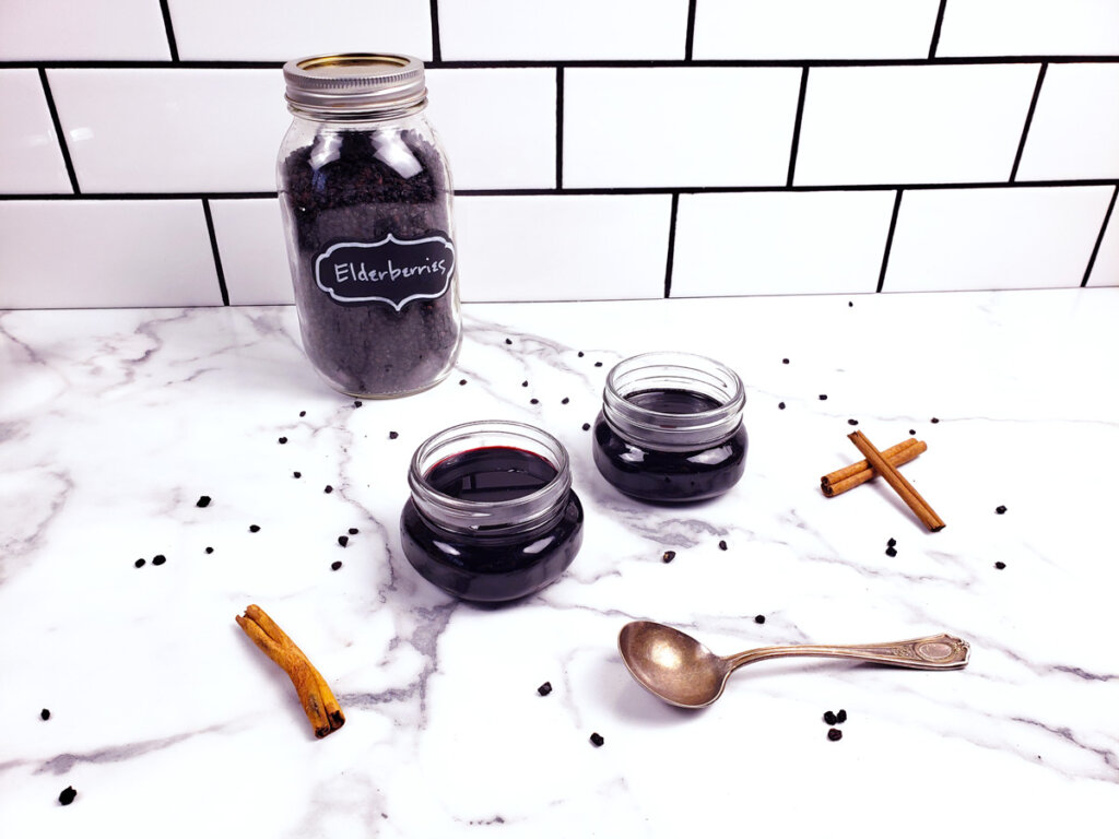 Dried elderberries in a jar and two small jars of elderberry syrup sitting on a counter.