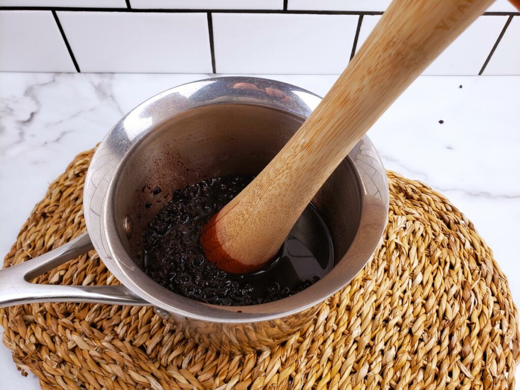 Elderberries being mashed with a kraut pounder.