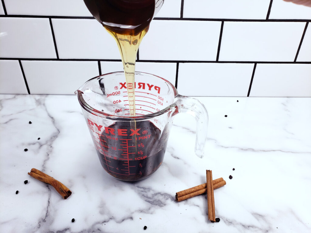 Honey being added to a measuring cup filled with elderberry syrup.