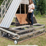 Pinterest pin with an image of a woman standing on a moveable chicken coop.