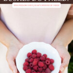 Pinterest pin for how many fruit and berry bushes to plant. Image of a woman holding a bowl full of fresh raspberries.