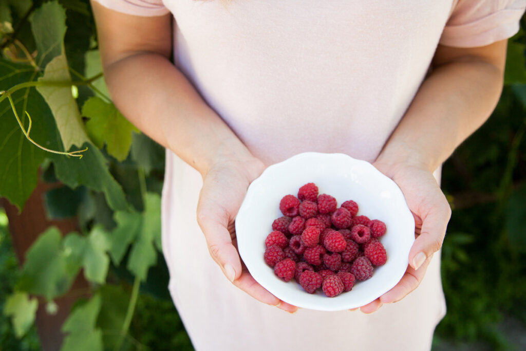 A woman holding a white bowl full of raspberries.