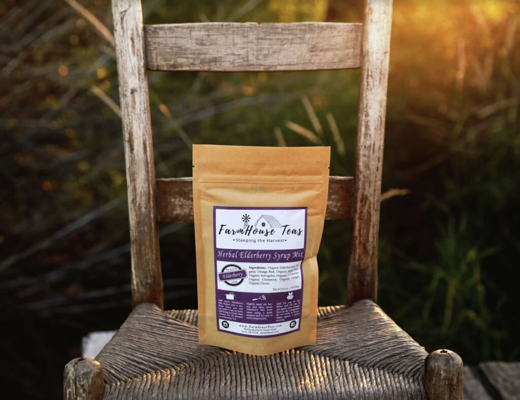 A bag of Herbal Elderberry Syrup Mix from Farmhouse Teas sitting on a chair in a field.