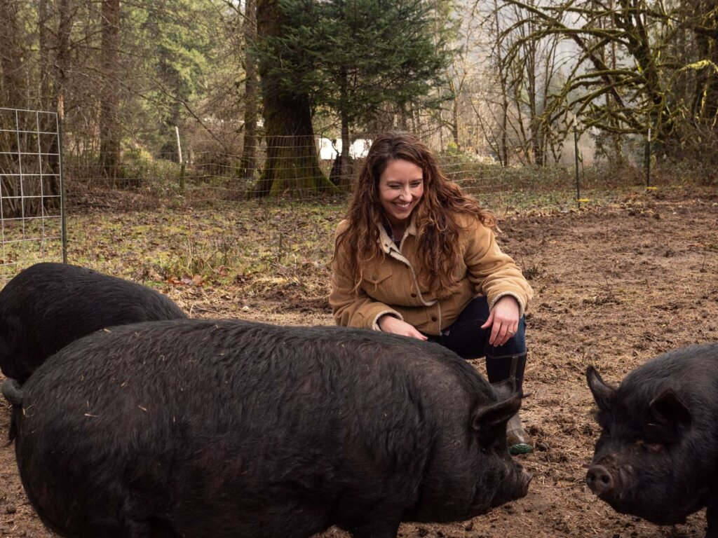 A woman laughing while petting pigs.