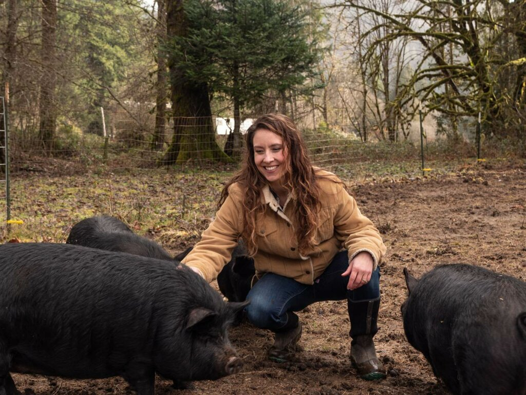 A woman squatting next to american guinea hogs.