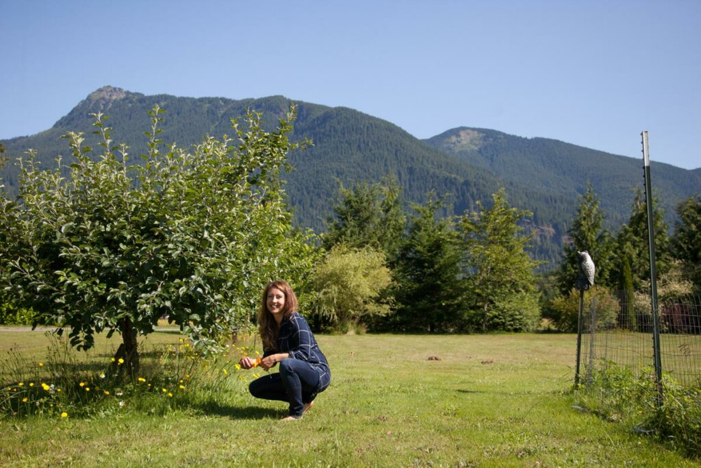 A woman crouched down next to an established fruit tree with mountains in the background.