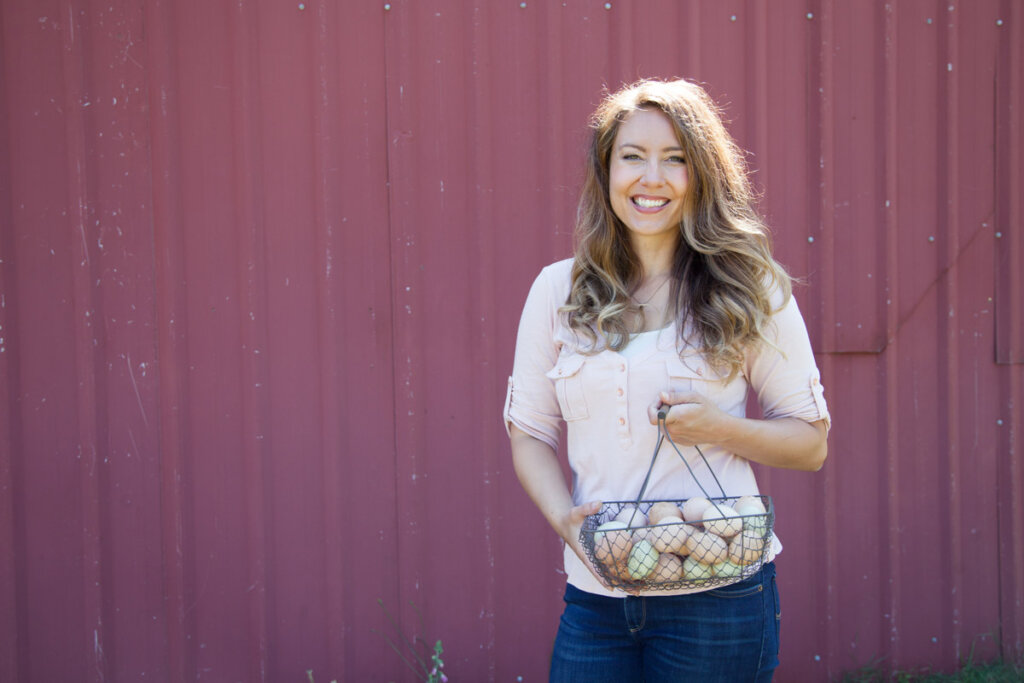 A woman standing in front of a red barn holding up a wire basket full of farm fresh eggs.