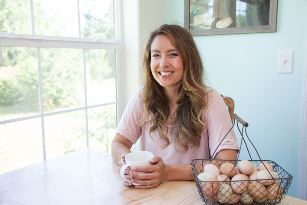 A woman sitting at her kitchen table with a cup of coffee next to a wire basket filled with farm fresh eggs.