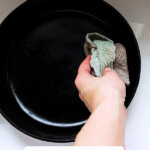 Pinterest pin for how to clean cast iron with an image of a dirty cast iron pan being cleaned.