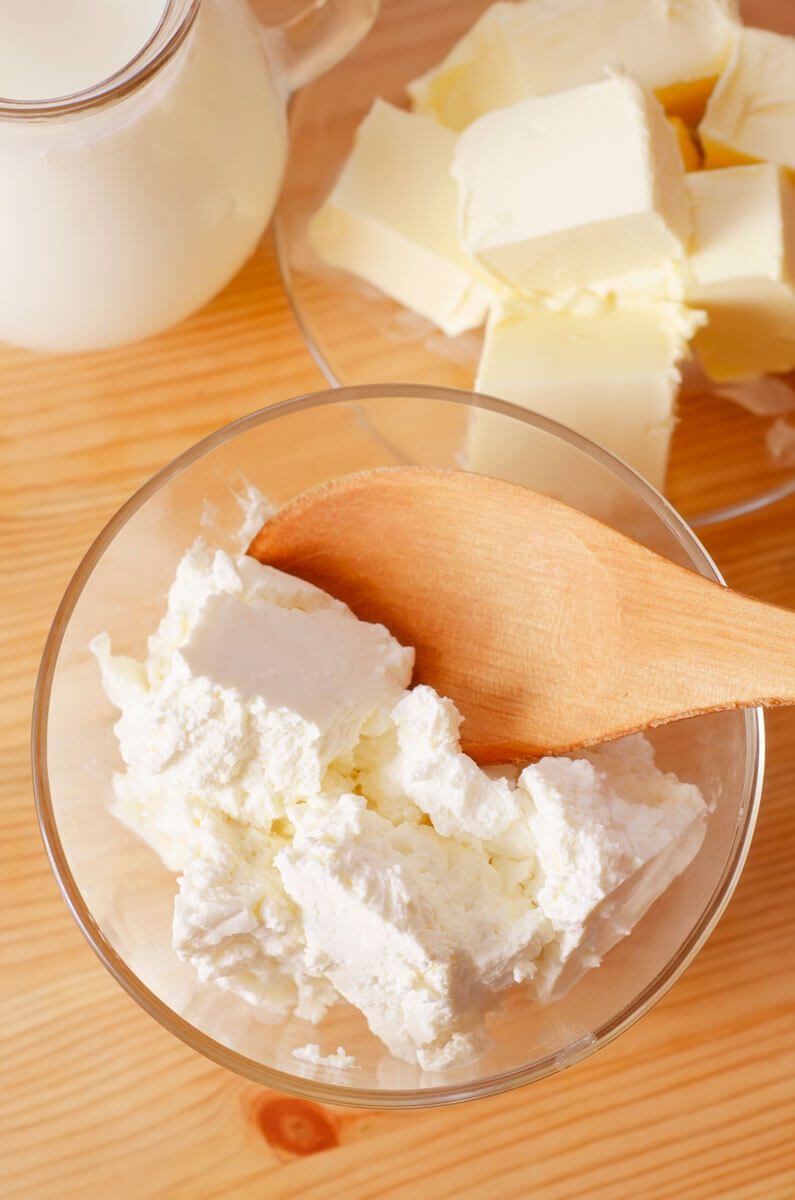 A bowl of cultured cheese with a wooden spoon.