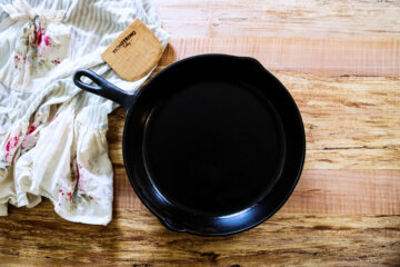 A clean cast iron pan sitting on a wooden counter top with a towel and a wooden bench scraper beside it.