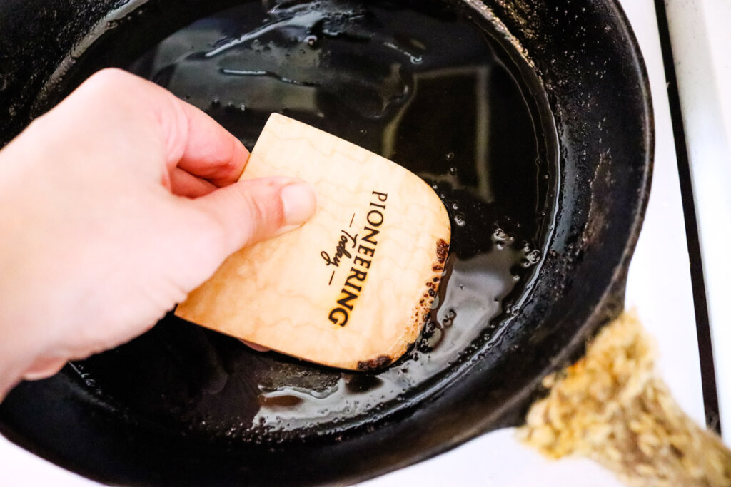 A cast iron pan being cleaned with a wooden bench scraper.