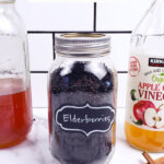 Pinterest pin for elderberry recipes with an image of elderberries in a glass jar.