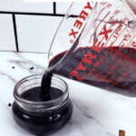 Pinterest pin for elderberry recipes with an image of elderberry syrup being poured into a jar.