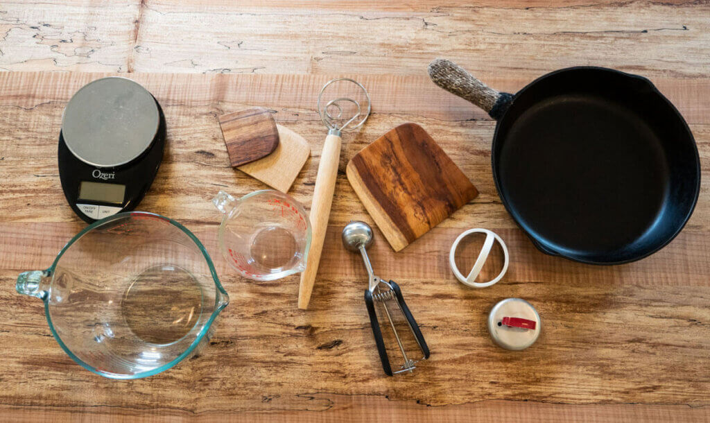 Image of 11 different kitchen tools sitting on a wooden counter top.