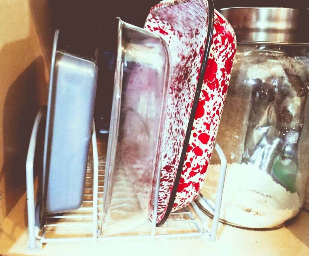Pots and pans organized in a kitchen cupboard with a rack organizer.