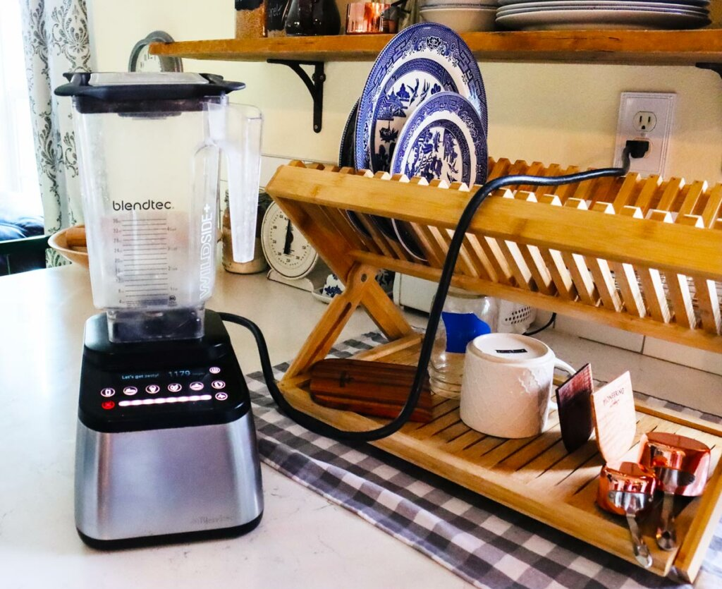 A BlendTec blender on the kitchen counter next to a wooden drying dish rack.
