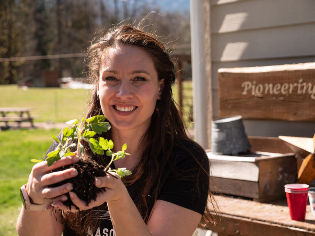 A woman holding seedlings in her hands, standing outside by a potting bench.