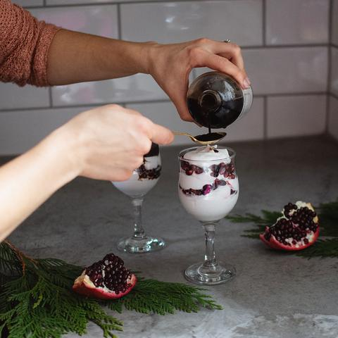 A woman pouring elderberry syrup onto a spoon with an elderberry fool on the counter.