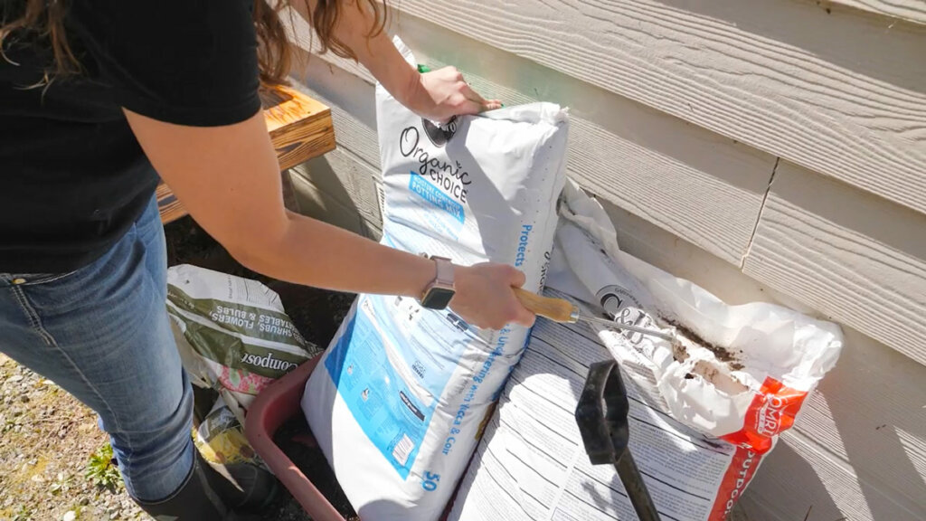 A woman opening a bag of potting soil.