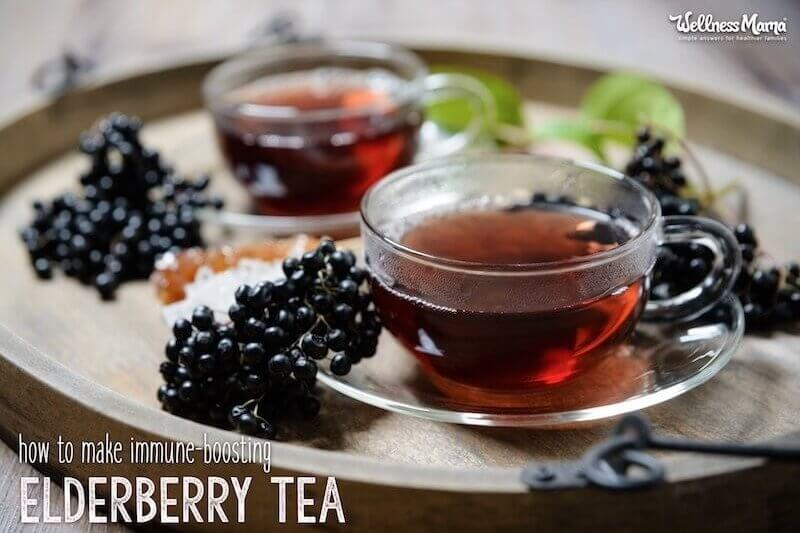 Two glasses of elderberry tea on a tray with fresh elderberry clusters.