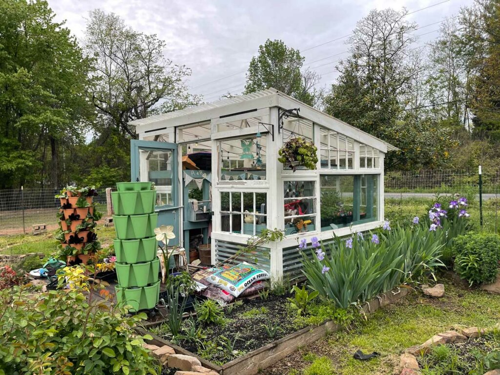 Image of a greenhouse with plants all around it.