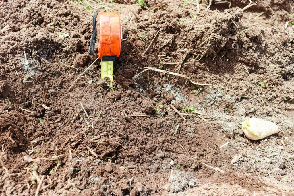 Image of a tape measure in the ground with dirt piled up about six inches.
